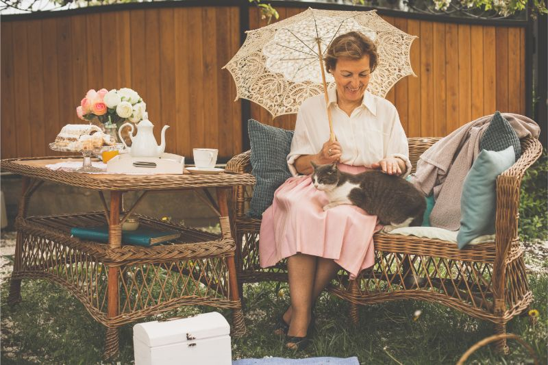 An older woman sits in her garden with her cat on her lap